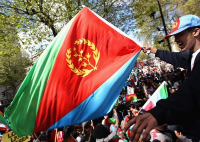 LONDON, ENGLAND - APRIL 30: An Eritrean demonstrator waves his national flag whist taking part in a demonstration on Whitehall on April 30, 2012 in London, England. The protesters were demanding that Britain stops selling arms to Ethiopia, their neighboring country, and for Ethiopian nationals to leave Eritrea. (Photo by Dan Kitwood/Getty Images)