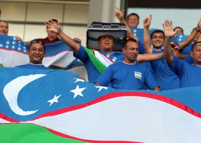 Uzbekistan fans hold up their national flag as they watch their national team play against Qatar during their group B 2014 World Cup Asian qualifying football match in Doha on October 16 , 2012. AFP PHOTO/KARIM JAAFAR ==QATAR OUT==        (Photo credit should read KARIM JAAFAR/AFP/Getty Images)