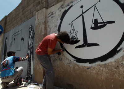 Yemeni artists finish graffitis against corruption in Yemen on a wall in the capital Sanaa on June 5, 2014. AFP PHOTO / MOHAMMED HUWAIS        (Photo credit should read MOHAMMED HUWAIS/AFP/Getty Images)