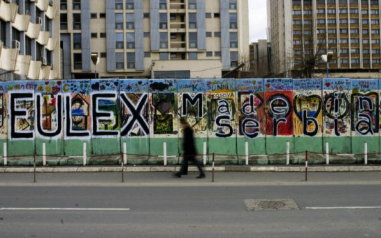 "Kosovo Albanians walks by a grafiti, reading ""Eulex made in Serbia,"" in the Kosovar capital of Pristina on December 8, 2008.The EU agreed in February 2008 to send the 2,000-strong EULEX mission to Kosovo to gradually replace a United Nations operation and oversee the police, judiciary and customs. The UN Security Council last week gave a green light to the planned EU mission, which is likely to start its operation in Kosovo on December 9, 2008 under the UN umbrella.AFP PHOTO/ARMEND NIMANI (Photo credit should read Armend Nimani/AFP/Getty Images)"